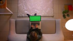 Tiro superior do close up da datilografia f?mea bonita nova no port?til com tela verde ao sentar-se no sof? dentro em
