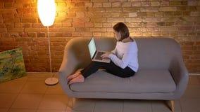 Tiro superior do close up da datilografia fêmea caucasiano nova no portátil ao sentar-se no sofá na casa acolhedor dentro filme