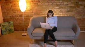 Tiro superior do close up da datilografia fêmea caucasiano nova no portátil e de fazer o trabalho remoto da casa que senta-se no  filme