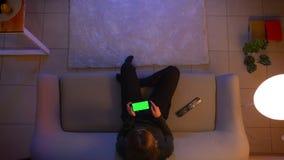 Tiro superior do close up da fêmea bonita nova que olha uma propaganda no telefone com a tela verde na frente da tevê e video estoque