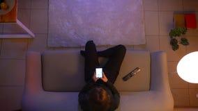 Tiro superior do close up da mensagem fêmea bonita nova no telefone na frente da tevê e do assento no sofá dentro em vídeos de arquivo