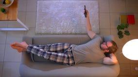 Tiro superior do close up da tevê de observação masculina ocasionalmente vestida nova que encontra-se no sofá e que usa o control video estoque