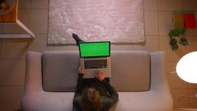 Tiro superior do close up da Web fêmea bonita nova da consultação no portátil com tela verde ao sentar-se no sofá dentro video estoque
