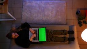 Tiro superior do close up de texting fêmea bonito no portátil com tela verde ao encontrar-se no sofá dentro em um acolhedor vídeos de arquivo