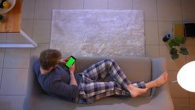 Tiro superior do close up de texting masculino ocasionalmente vestido novo no telefone com a tela verde que encontra-se no sofá d filme