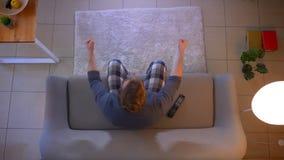 Tiro superior do close up do fósforo de futebol de observação masculino novo na tevê que senta-se no sofá que fica animado e que  vídeos de arquivo