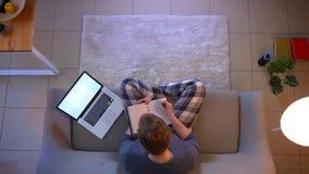 Tiro superior do close up do homem de negócios novo que trabalha e que toma notas usando o portátil ao sentar-se no sofá dentro e video estoque