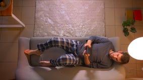 Tiro superior do close up do homem novo que consulta na tabuleta ao encontrar-se e ao descansar no sof? dentro na casa acolhedor filme