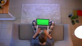 Tiro superior do close up do homem novo que estuda em linha usando o portátil com tela verde ao sentar-se no sofá dentro em video estoque