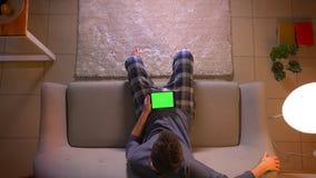 Tiro superior do close up do homem novo que olha uma propaganda a tabuleta com tela verde ao sentar-se no sofá dentro