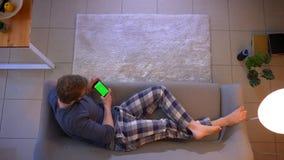 Tiro superior do close up do homem ocasionalmente vestido novo que olha uma propaganda no telefone com a tela verde que encontra- video estoque