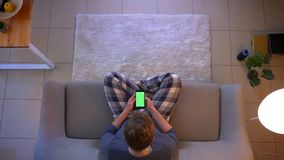 Tiro superior do close up do homem ocasionalmente vestido novo que olha uma propaganda no telefone que senta-se no sofá dentro em filme