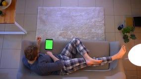 Tiro superior do close up do homem ocasionalmente vestido novo que usa a tabuleta com tela verde ao encontrar-se no sof? dentro e