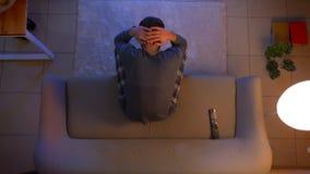Tiro superior do close up do homem triste novo que olha um f?sforo de futebol na tev? que senta-se no sof? que obt?m infeliz e fr video estoque
