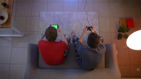 Tiro superior dos amigos na roupa de noite que joga o videogame com manche e que trabalha com o smartphone na sala de visitas video estoque