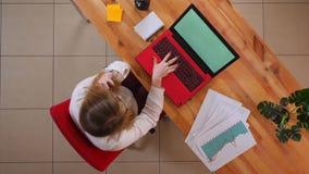 Tiro superiore del primo piano di giovane donna di affari caucasica che ha una telefonata che si siede davanti al computer portat video d archivio