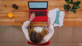 Tiro superiore del primo piano di giovane donna di affari caucasica in vetri facendo uso del computer portatile e di presa delle  video d archivio
