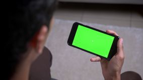 Tiro traseiro da opinião do close up da mão masculina que realiza um telefone com tela verde dentro no apartamento vídeos de arquivo