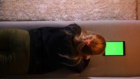 Tiro traseiro superior do close up da menina bonita que usa a tabuleta com tela verde ao encontrar-se no sof? dentro em um acolhe video estoque