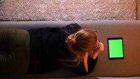 Tiro traseiro superior do close up da menina bonita que usa a tabuleta com a tela verde da croma-chave ao encontrar-se no sof? de vídeos de arquivo
