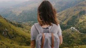 Tiro trasero medio de la visión, mujer feliz joven que camina con la mochila y pelo del vuelo que mira las montañas increíbles en almacen de video