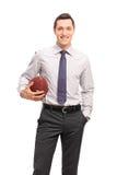Tiro vertical de um homem de negócios novo que guarda um futebol Foto de Stock