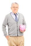 Tiro vertical de um homem maduro que guarda um piggybank Fotos de Stock