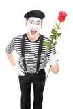 Tiro vertical de un artista del imitar que sostiene una rosa roja Imagenes de archivo