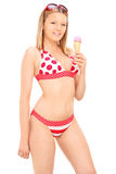 Tiro vertical de una mujer en bikini que come un helado Imagen de archivo