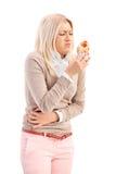 Tiro vertical de una mujer que come un perrito caliente y que siente enferma Fotos de archivo