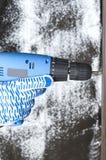 Tiro vertical Mão nas luvas que mantêm a chave de fenda contra o material de prata do hardware foto de stock
