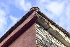 Tiro vicino dell'angolo del tetto della costruzione della muratura con il fondo blu del cielo aperto fotografie stock libere da diritti