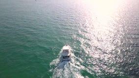 Tiro video aéreo con el abejón sobre el mar y playa con el barco y el yate