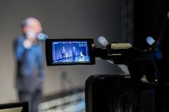 Tiro video do evento Câmara de vídeo com exposição do LCD 2 homens na fase na frente dos microfones em um fundo de tela cinzento fotos de stock