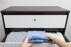 Tiroir ouvert de main de femme et prendre la serviette Photos stock