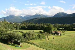 Tirol. Countryside in Tirol, Austria. Haystacks, small wooden buildings and mountains in the background. Region of Stubaital and Stubaier Alpen Royalty Free Stock Photo