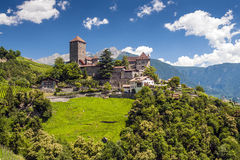 Tirol Castle. On a sunny summer day with blue sky, white clouds, green meadows and trees Stock Photo