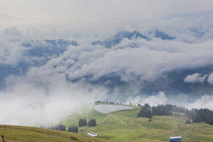 Tirolean Alps. The alps in tirol, green meadows, blue skies and mountains covered with clouds Royalty Free Stock Photo