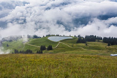Tirolean Alps. The alps in tirol, green meadows, blue skies and mountains covered with clouds Stock Photo