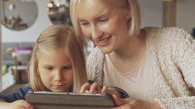 Tirones de la niña en la tableta en el café metrajes