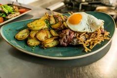 Tiroolse gebraden aardappels met vleesbacon, paddestoelen en een gebraden ei stock afbeelding