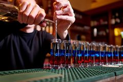 Tiros alcoólicos no contador da barra O barman profissional derrama tiros alcoólicos fotografia de stock royalty free
