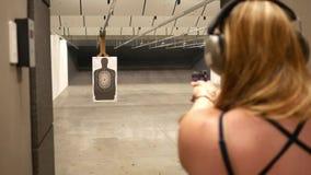 Tiros da mulher em um alvo de um homem em uma escala de acendimento interna do tiro da arma vídeos de arquivo