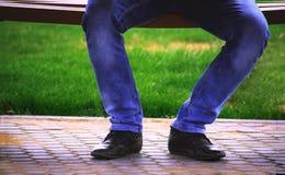 Tiros de las piernas de un hombre que se sienta en un banco Foto de archivo