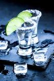 Tiros de prata do tequila com gelo e cal no fundo preto da tabela Imagem de Stock