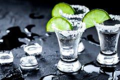 Tiros de prata do tequila com gelo e cal no fundo preto da tabela Foto de Stock Royalty Free