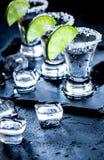 Tiros de prata do tequila com gelo e cal no fundo preto da tabela Fotos de Stock
