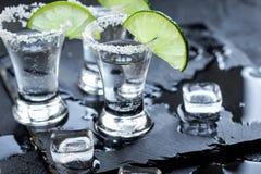 Tiros de prata do tequila com gelo e cal no fundo preto da tabela Imagens de Stock