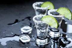 Tiros de prata do tequila com gelo e cal no fundo preto da tabela Imagem de Stock Royalty Free