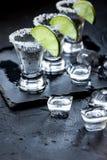Tiros de prata do tequila com gelo e cal no fundo preto da tabela Fotografia de Stock Royalty Free